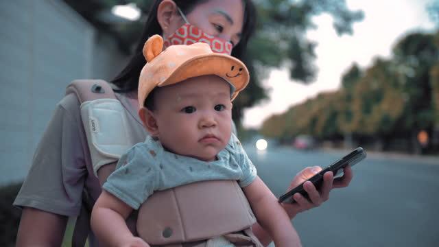 vídeos de stock, filmes e b-roll de mulher asiática e filho mensagens com telefone inteligente na rua urbana à noite - 6 11 months