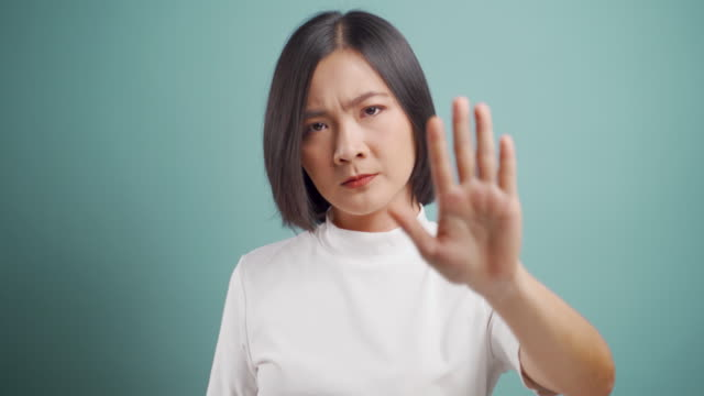 asian woman  angry and showing hand make stop sign and standing isolated over blue background. health care concepts. 4k video. - stop sign stock videos & royalty-free footage