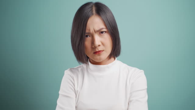asian woman  angry  looking at camera and standing isolated over blue background. health care concepts. 4k video. - facial expression stock videos & royalty-free footage