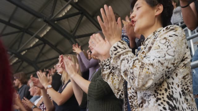 Asian woman applauding standing on the stadium tribune