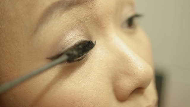 asian woman applying eye make up - mascara bildbanksvideor och videomaterial från bakom kulisserna