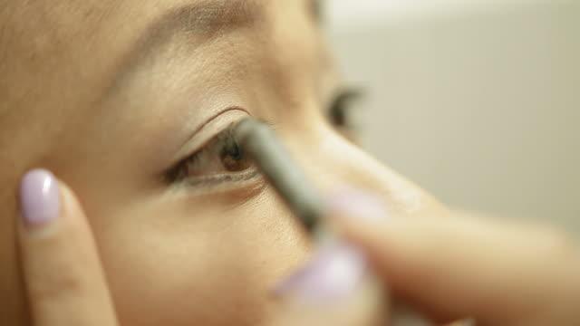 Asian woman applying eyeliner close up shot
