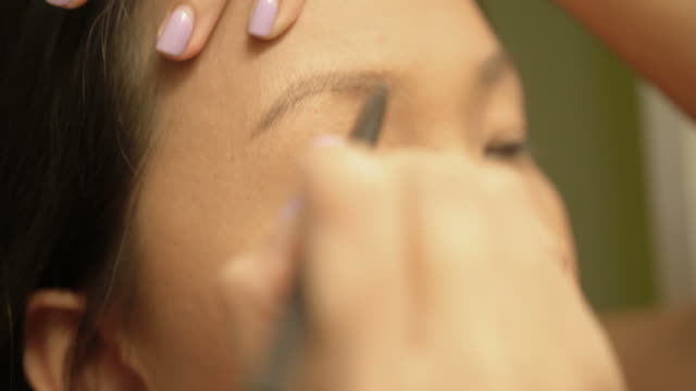 Asian woman applying make up