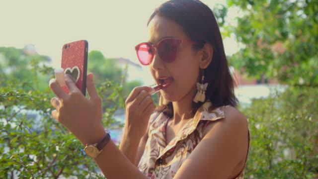 vidéos et rushes de femme asiatique appliquant rouge à lèvres et regardant un maquillage à son téléphone portable. belle femme portraits avec fashionista look. - rouge à lèvres rouge