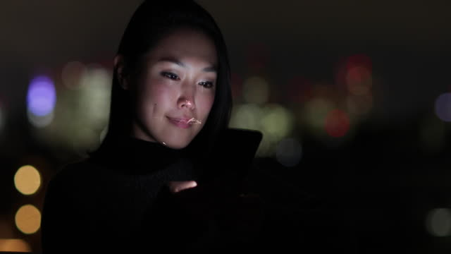 stockvideo's en b-roll-footage met asian woman at night using facial recognition technology to unlock smart phone on street - identity