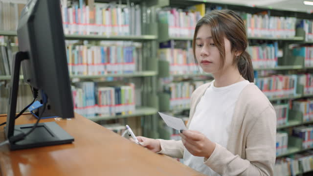 asian woman at the library searching through database for a book on computer - collection stock videos & royalty-free footage