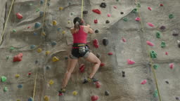 Asian woman athlete climbing on indoor wall