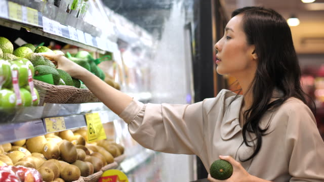 asian woman avocado fruit shopping in supermarket - merchandise stock videos & royalty-free footage