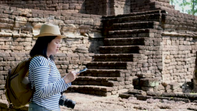 Asian woman backpack traveler use map at ancient of pagoda temple thai architecture at Sukhothai,thailand.Holiday vacation concept.journey lifestyle