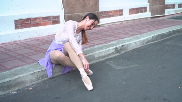 asian woman ballet dancer sitting on footpath, lancing rope on the shoe before practicing ballet on a local street as a classroom on a sunny day with enjoyment and happiness. concept of the active young teenager on weekend activities. - ballet shoe stock videos & royalty-free footage