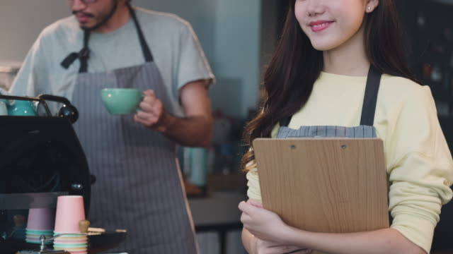 asian woman barista holding menu and smiling to customer at cafe counter bar inside coffee shop, food and drink business start up.small business.close up shot - coffee drink stock videos & royalty-free footage
