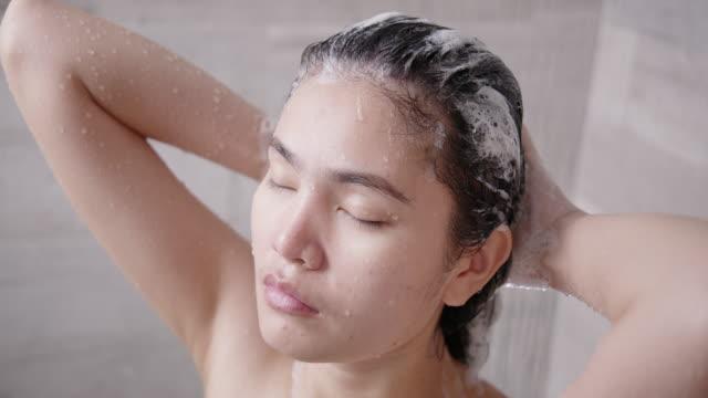 vídeos de stock e filmes b-roll de asian woman bathing and washing her hair. - champô