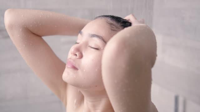 vídeos de stock, filmes e b-roll de mulher asiática tomando banho e lavando o cabelo. - lazer