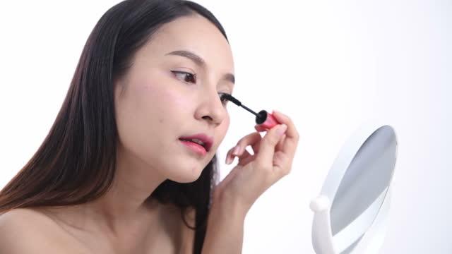 アジアの女性ブロガーは、化粧品を作り上げ、使用する方法を示しています。スタジオでvlogビデオライブストリーミングを記録するためにカメラの前で - 口紅点の映像素材/bロール