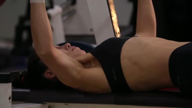 vídeos de stock e filmes b-roll de a asian woman body builder doing bench press at the gym - só uma mulher de idade mediana