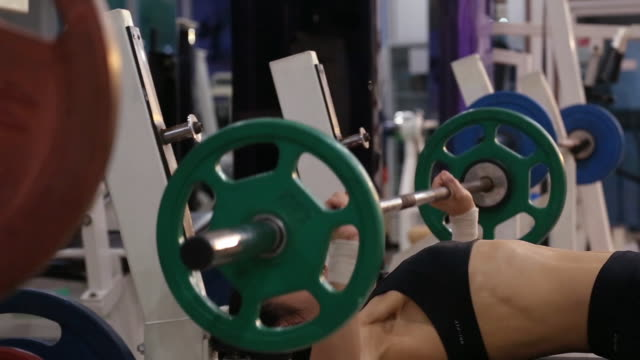 A asian woman body builder doing bench press at the gym