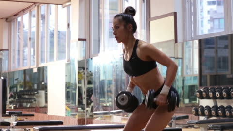a asian woman body builder doing bent-over row dumbbell at the gym - weight training stock videos & royalty-free footage