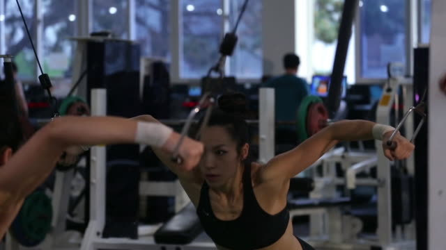 A asian woman body builder doing cable cross-over at the gym