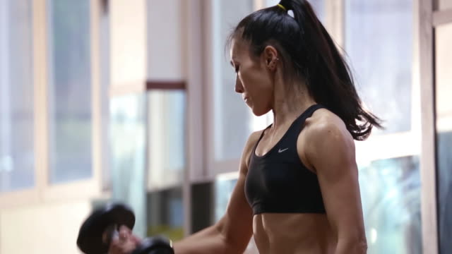 a asian woman body builder doing dumbbell curl at the gym - weight training stock videos and b-roll footage
