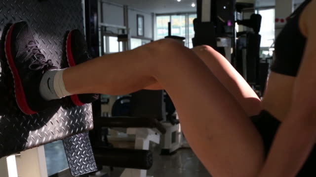 a asian woman body builder doing leg press at the gym - レッグプレス点の映像素材/bロール