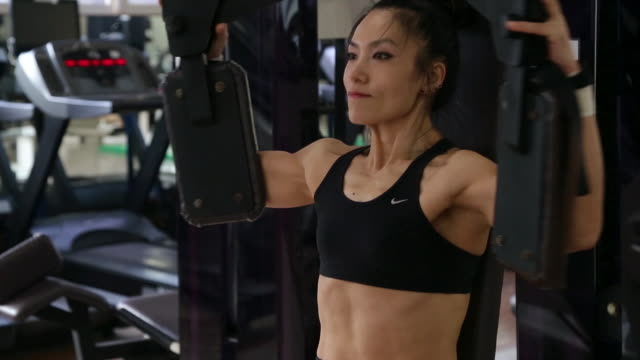 a asian woman body builder doing machine flys at the gym - asian stock videos & royalty-free footage