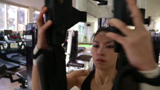 A asian woman body builder doing Machine Flys at the gym
