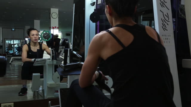 A asian woman body builder doing relaxation during exercise at the gym