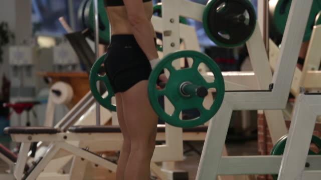 a asian woman body builder doing romanian deadlift at the gym - ウエイトトレーニング点の映像素材/bロール
