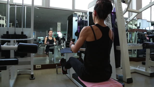A asian woman body builder doing Rowing Machine at the gym