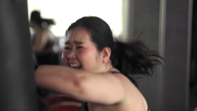 asian woman boxing punshing bag - overweight active stock videos & royalty-free footage