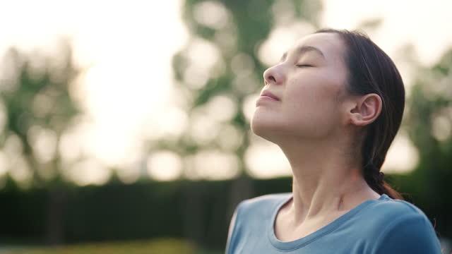 アジアの女性は新鮮な空気を呼吸します - inhaling点の映像素材/bロール