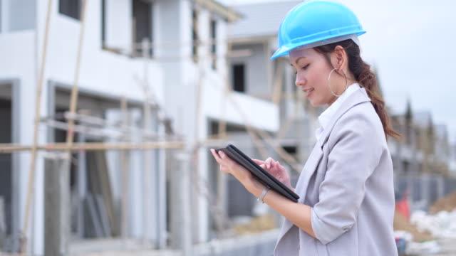 タブレット上の情報をチェックするアジアの女性の建物の検査官 - ヘルメット点の映像素材/bロール