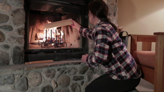 asian woman burning logs in the fireplace at a winter lodge - chinaface stock videos & royalty-free footage