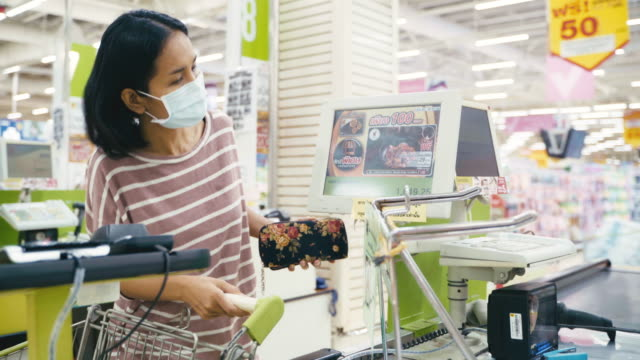 asian woman buying and paying the goods in the store with face mask protection from corona virus and flu for healthy life. - till stock videos & royalty-free footage