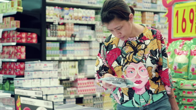 asian woman buying frozen food in supermarket. - packaging stock videos & royalty-free footage