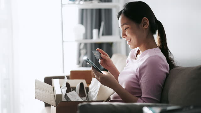 asian woman buying online shopping entering pin numbers on mobile phone and holding credit card at home - home shopping stock videos & royalty-free footage