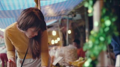 vidéos et rushes de asiatique femme fraise sur un marché d'achat - freshness