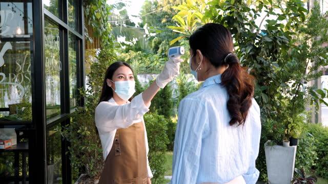 アジアの女性カフェの従業員は、新しい通常のライフスタイルコロナウイルスcovid-19パンデミックのためにレストランやコーヒーカフェに行く前に、フェイスマスクで温度アジアの男性を取� - 温度計点の映像素材/bロール