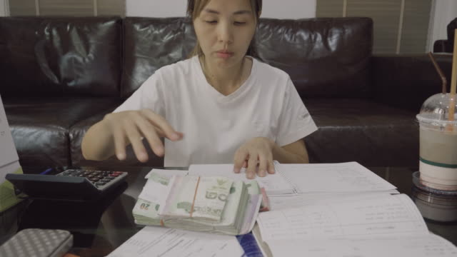 asian woman calculating in home - home economics class stock videos & royalty-free footage