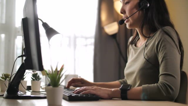 asian woman call center at home - cuffia attrezzatura per l'informazione video stock e b–roll