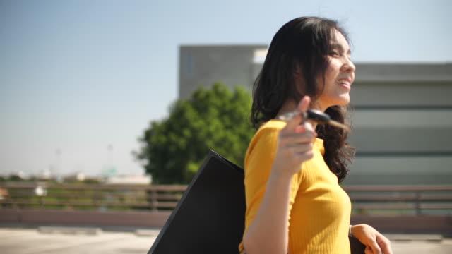stockvideo's en b-roll-footage met aziatische vrouw het dragen van boodschappentassen en sleutelhanger wandelen - parkeren