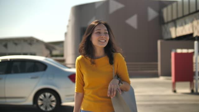 donna asiatica che porta borse della spesa e portachiavi a piedi - parking video stock e b–roll