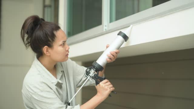 asian woman caulking outside window - sigillante video stock e b–roll