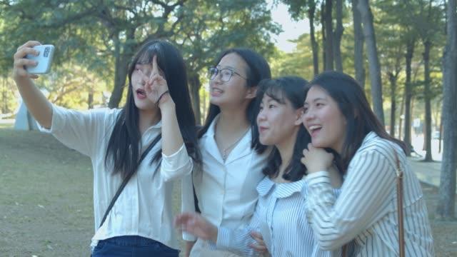 公園でおしゃべりアジアの女性 - ヤングアダルト点の映像素材/bロール