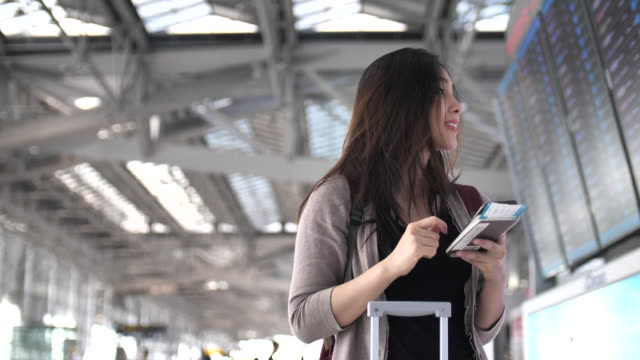 vídeos de stock e filmes b-roll de asian woman check flight schedule at schedule display in the airport - explorador