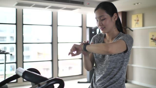 運動中のスマートな腕時計にアジア女性チェック心拍数モニター - エアロバイク点の映像素材/bロール