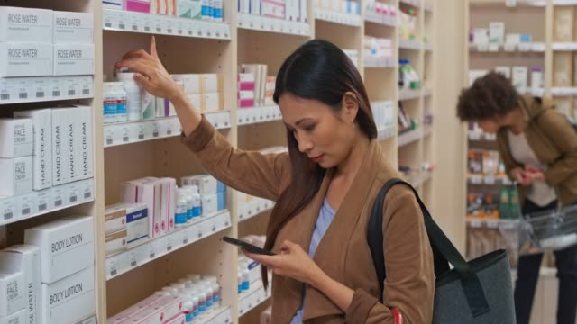 ds asian woman checking her phone before taking a medicine bottle from the shelf at the drugstore - merchandise stock videos & royalty-free footage