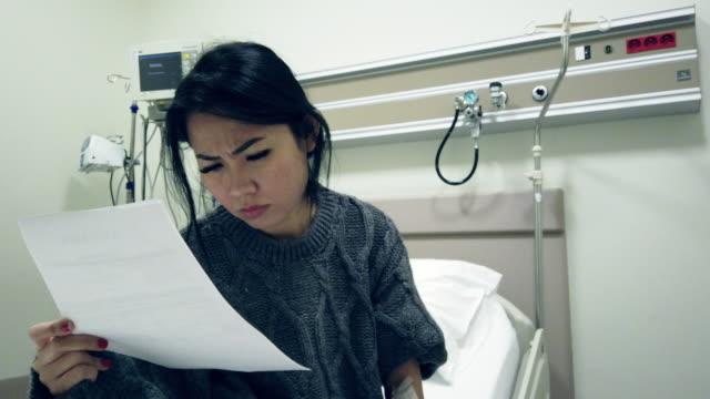 donna asiatica che controlla l'esame medico di coronavirus covid-19 quarantena in ospedale - citochinesi video stock e b–roll