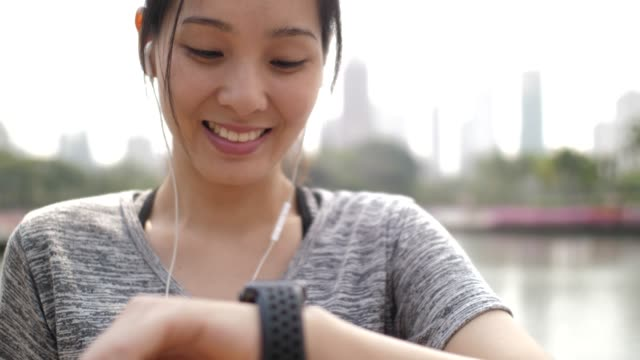 Asian Woman checking pulse on Smart watch