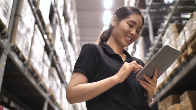 asian woman checking supplies on digital tablet in the warehouse - electronic organiser stock videos & royalty-free footage